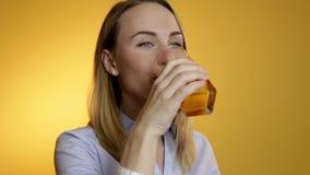 Attraktiv härlig ung kvinna som dricker fruktsaft från ett exponeringsglas på en gul bakgrund stock video