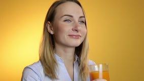 Attraktiv härlig ung kvinna som dricker fruktsaft från ett exponeringsglas på en gul bakgrund lager videofilmer