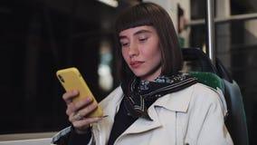 Attraktiv hållande ögonen på video för ung kvinna på smartphonen på kollektivtrafik san f?r natt f?r fj?rdbroca francisco tid N?r arkivfilmer