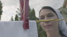 Attraktiv hög kvinna med en vit sjal på hennes hängande vita kläder för huvud på en klädstreck genom att använda klädnypan utomhu lager videofilmer