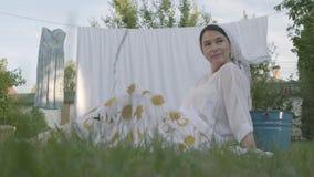 Attraktiv hög kvinna med en vit sjal på hennes huvud som vilar i trädgården som framme sitter på gräset av stock video