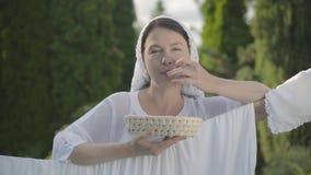 Attraktiv hög kvinna med sjalen på hennes huvud som äter paprika som ser kameran som ler över klädstrecket stock video