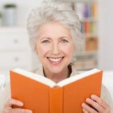 Attraktiv hög kvinna som läser en bok royaltyfria foton