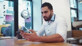 Attraktiv idrotts- affärsman i den stilfulla dräkten som rymmer hans telefon, smsar och har en morgonkopp kaffe arkivfilmer