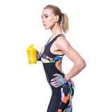 Attraktiv idrotts- kvinna som kopplar av efter genomkörare med shaker som isoleras över vit bakgrund Den sunda flickan dricker va Royaltyfri Foto