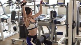 Attraktiv idrottskvinna som gör en övning på en utbildningsapparatur i idrottshallen flicka som gör en övning på musklerna av lager videofilmer