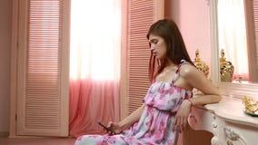 Attraktiv innehav för ung kvinna och användamobiltelefon hemma arkivfilmer