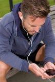 Attraktiv jogger som utanför lyssnar till musik Arkivbild