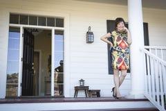Attraktiv kinesisk kvinna på hennes Front Porch Royaltyfria Bilder