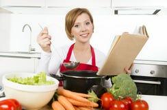 Attraktiv kockkvinna som förbereder kokboken för recept för grönsakragusoppa den läs- på inhemskt kök Royaltyfri Bild