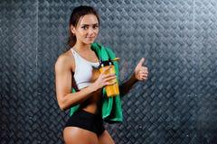Attraktiv konditionkvinna med den inomhus ståenden för flaska och för handduk Arkivbild