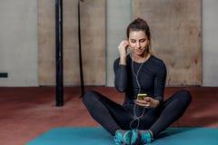 Attraktiv konditionkvinna med spelaren mp3 på mattt Royaltyfria Bilder