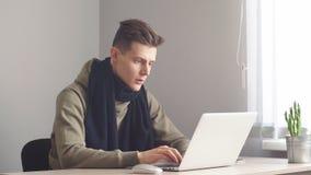 Attraktiv kontorsarbetare som hårt arbetar på hans kabinett som programmerar något på hans dator lager videofilmer