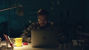 Attraktiv kontorsarbetare som hårt sent arbetar på hans kabinett på natten, drinkte och programmerar något på hans dator arkivfilmer