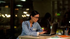 Attraktiv kontorsarbetare som skriver p? b?rbara datorn p? natten, internetforskning, jobb arkivfoto