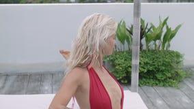 Attraktiv kvinna för blont hår i den praktiserande yogan för röd baddräkt på den öppna verandan av hotellet arkivfilmer