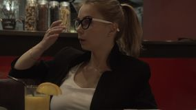 Attraktiv kvinna för stående i sexiga exponeringsglas som rymmer i handmobiltelefon stock video
