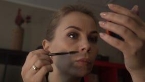 Attraktiv kvinna för stående som använder den kosmetiska borsten för sminkögonbryn lager videofilmer