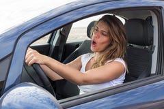 Attraktiv kvinna, i att sjunga för bil arkivfoto