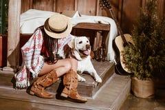 Attraktiv kvinna i bohostilsammanträde med en hund i a arkivbilder