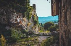 Attraktiv kvinna i den forntida fästningen för Stari stång, Montenegro Brunettflickan med långt hår i klänning går runt om det ga Royaltyfri Foto