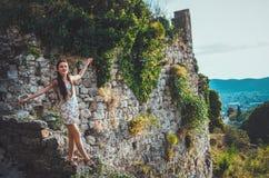 Attraktiv kvinna i den gamla fästningen för Stari stång, Montenegro Brunettkvinnlign i den vita klänningen går runt om slotten, m Royaltyfri Foto