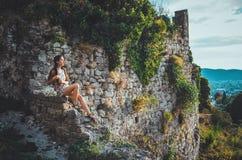 Attraktiv kvinna i den gamla fästningen för Stari stång, Montenegro Brunettkvinnlign med långt hår i klänning går runt om slotten Royaltyfri Foto