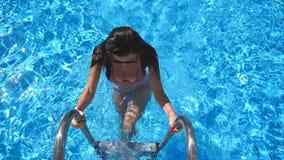 Attraktiv kvinna i den rosa bikinin som får ut ur pöl Ung sexig flicka som tycker om sommarsemestern som förnyar i handfat lady lager videofilmer