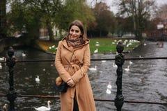 Attraktiv kvinna i det bruna laganseendet på bron, bakgrund av floden med svanar royaltyfri foto