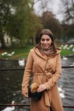 Attraktiv kvinna i det bruna laganseendet på bron, bakgrund av floden med svanar arkivfoton