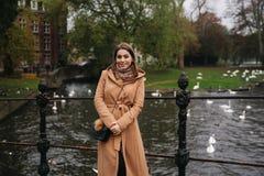 Attraktiv kvinna i det bruna laganseendet på bron, bakgrund av floden med svanar fotografering för bildbyråer