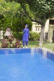 Attraktiv kvinna i en muslimsk swimwearburkini på en pölsida i en tropisk trädgård Royaltyfri Foto