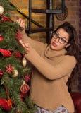 Attraktiv kvinna i exponeringsglas som dekorerar julträdet Royaltyfri Fotografi