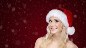 Attraktiv kvinna i jullock på snöig bakgrund arkivfoto