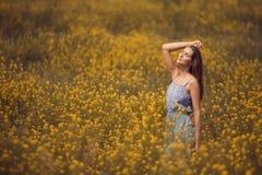 attraktiv kvinna i klänning på blommafältet royaltyfri bild