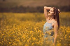 attraktiv kvinna i klänning på blommafältet royaltyfri fotografi