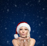 Attraktiv kvinna i kyss för jullockblows royaltyfri fotografi