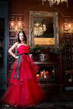 Attraktiv kvinna i lång röd klänning i lyxig inre retro tappningstil arkivfoto