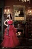 Attraktiv kvinna i lång röd klänning i lyxig inre retro tappningstil royaltyfri fotografi