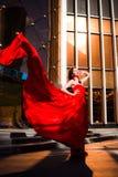 Attraktiv kvinna i röd fladdrad klänning Brand flamma, passionbegrepp royaltyfria bilder