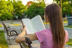 Attraktiv kvinna i röd och vit t-skjorta som tycker om en bok på bänken i parkera i sommardag Den härliga flickan kopplar av och  royaltyfri foto