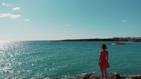 Attraktiv kvinna, i rött klänninganseende på den steniga klippan i medelhavet och att se blå havsvatten och himmel Surrsikt av gi arkivfilmer