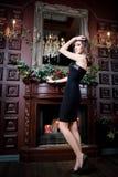 Attraktiv kvinna i svart klänning i lyxig inre Slott Arkivfoto