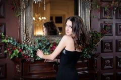 Attraktiv kvinna i svart klänning i lyxig inre Slott Arkivbild