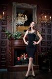 Attraktiv kvinna i svart klänning i lyxig inre Slott Fotografering för Bildbyråer