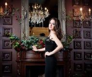 Attraktiv kvinna i svart klänning i lyxig inre Slott Royaltyfri Bild