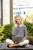 Attraktiv kvinna med bärbara datorn och behändigt royaltyfri fotografi