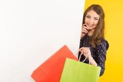Attraktiv kvinna med baner- och shoppingpåsar royaltyfri bild