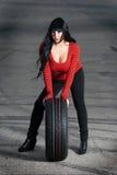 Attraktiv kvinna med bilgummihjulet Arkivbild