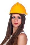 Attraktiv kvinna med blåa ögon och den gula hjälmen royaltyfria bilder